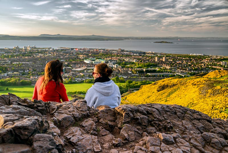 Two girls sitting on the hill of Arthur's Seat overlooking Edinburgh. The hills are covered in yellow wild flowers and the sky is cloudy and moody.