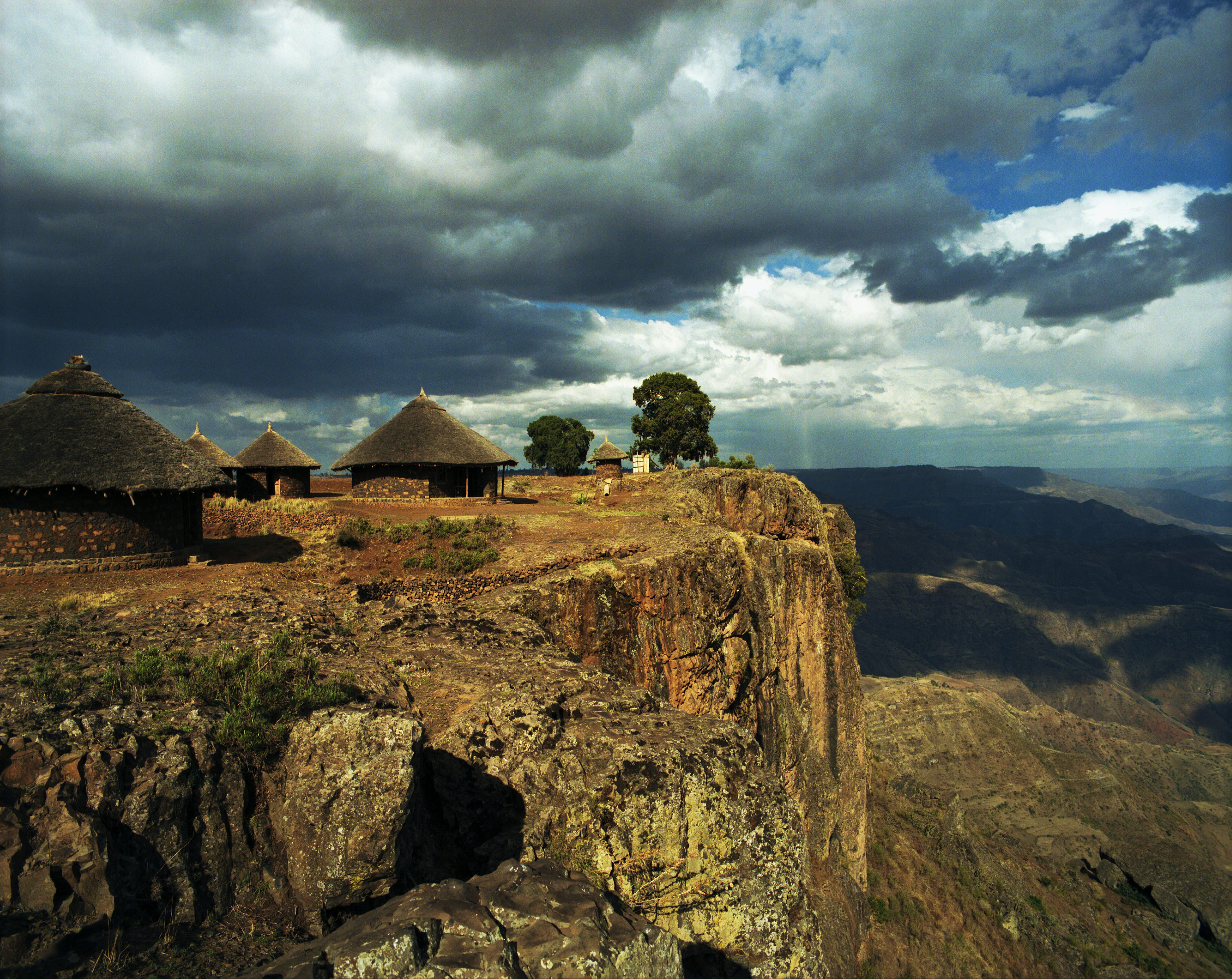 Traditional Ethiopian houses called tukuls sit on a cliff overlooking a deep valley