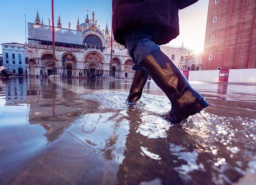 Một người đi ủng cao su sải bước qua dòng nước lũ đi về phía một tòa nhà được trang trí công phu ở rìa quảng trường lớn