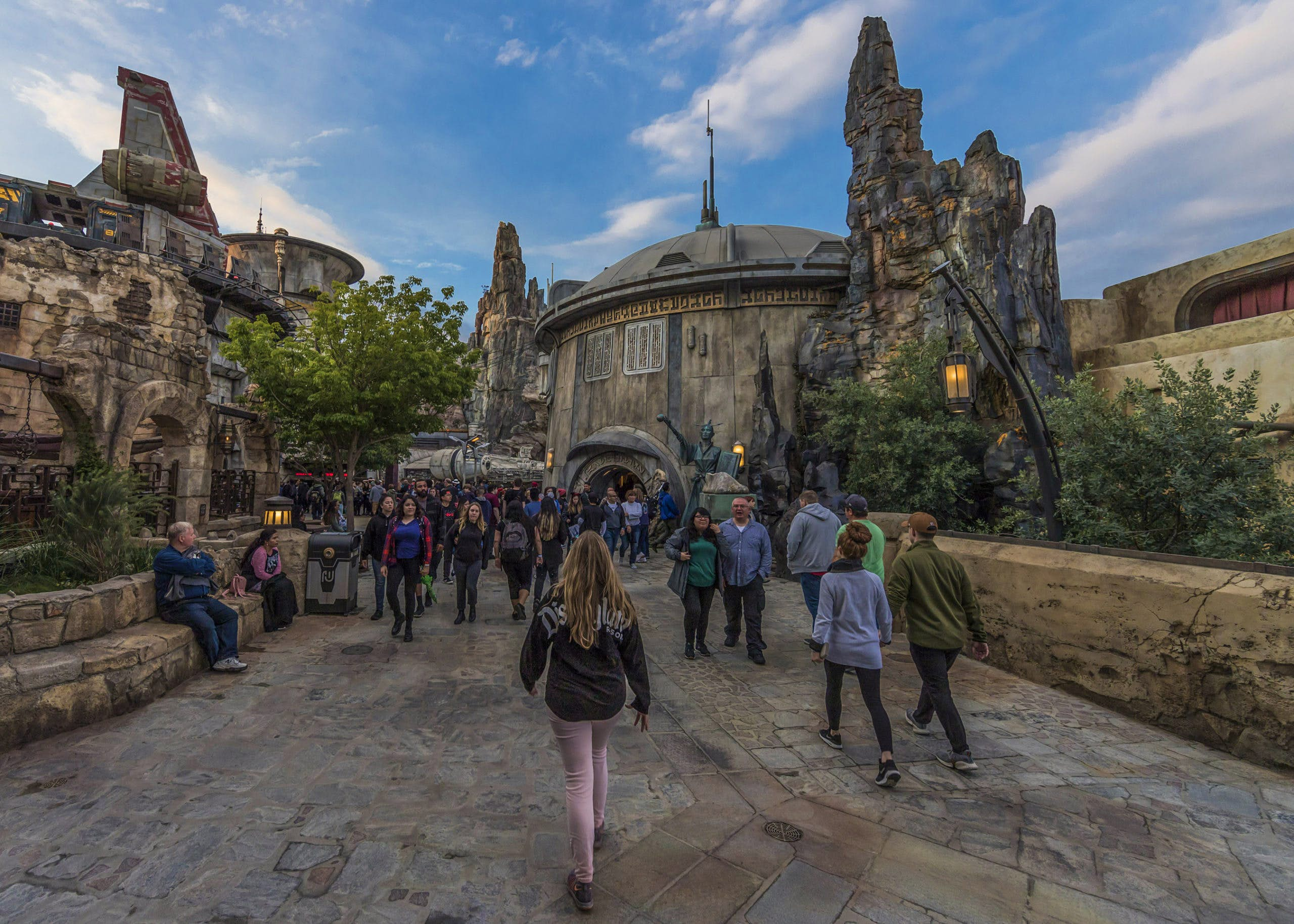 Guests wander through a replica of Black Spire Outpost, a village on the planet of Batuu, at Disneyland