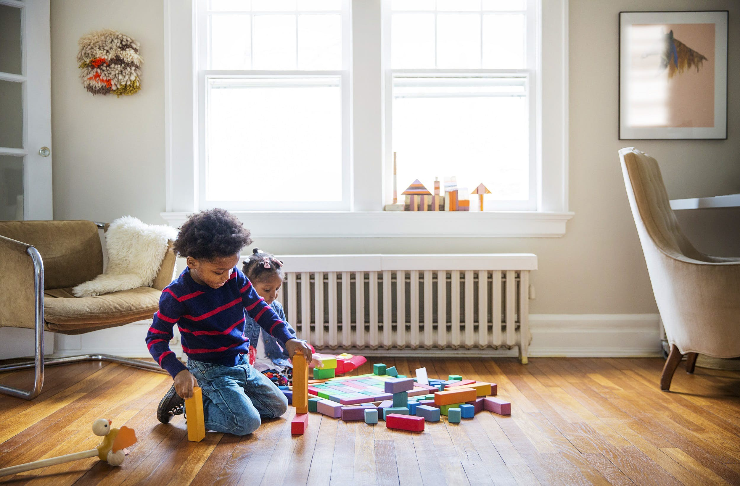 Two young children sit on a wooden floor surrounded by colourful blocks. The oldest child has built a tower