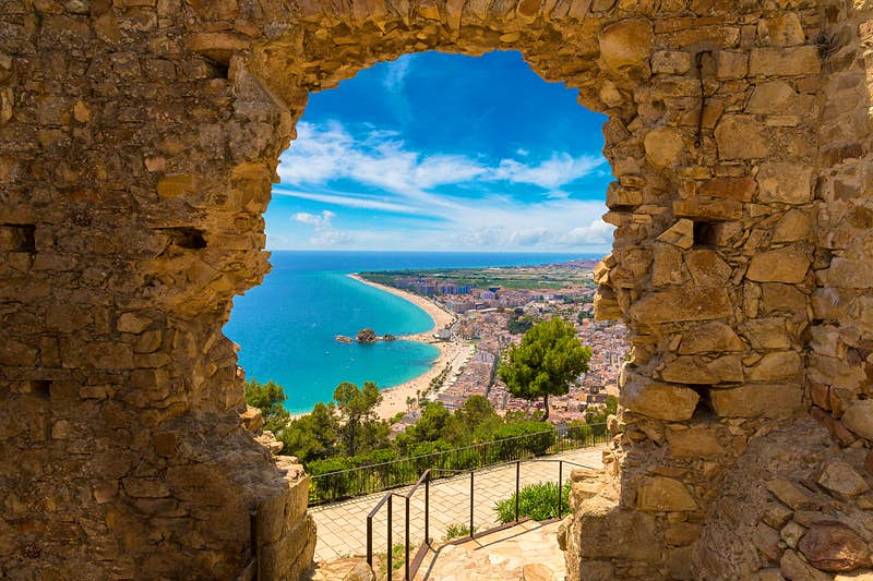 And aerial image of Blanes beach in the distance, through a stone door of St John Castle high above town.