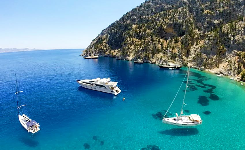 Several white, wedge-shaped boats, one a yacht, one a sail boat, and several too far in the distance to quite make out, sit on deep blue and turquoise waters off the rocky, hilly shores of Greece, which are light brown and dotted with scraggly scrub trees.