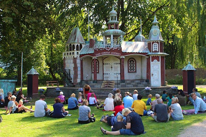 As famílias estão sentadas na grama em um parque na ilha Eventyrhaven, de frente para o palco do castelo em miniatura Hans Christian Andersen.