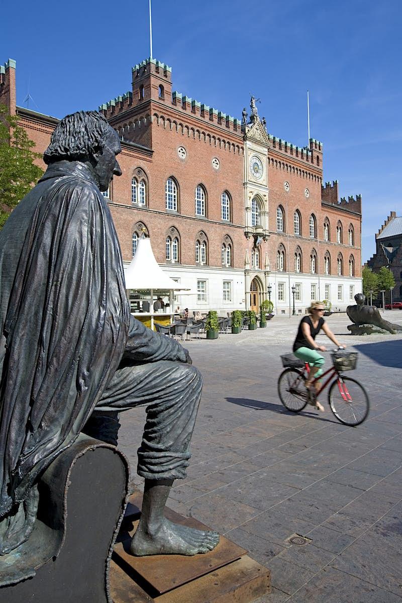 Uma estátua sentada de Hans Christian Andersen em uma grande praça pública em Odense, na Dinamarca; uma mulher está andando de bicicleta pela moldura em frente à estátua.