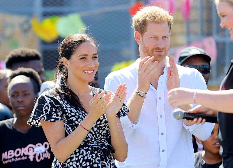 Meghan Markle and Prince Harry stand side by side, clapping as they look on at a performance.