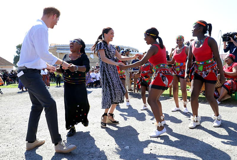 Prince Harry dances with a woman while his wife Meghan dances with some girls.