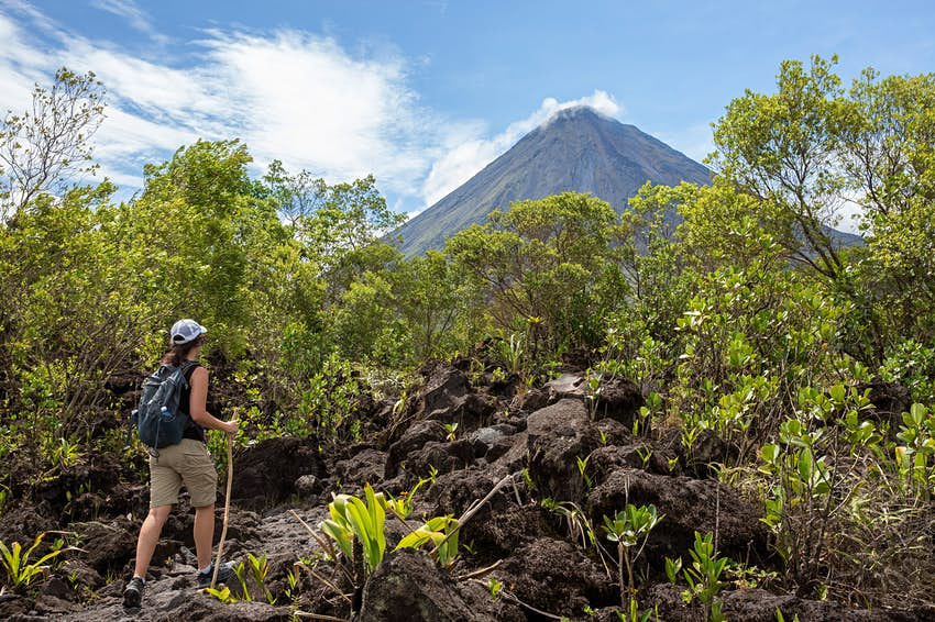 A woman hikes through volcanic boulders towards the treeline; in the distance are the steep slopes of Arenal volcano rising into the sky.