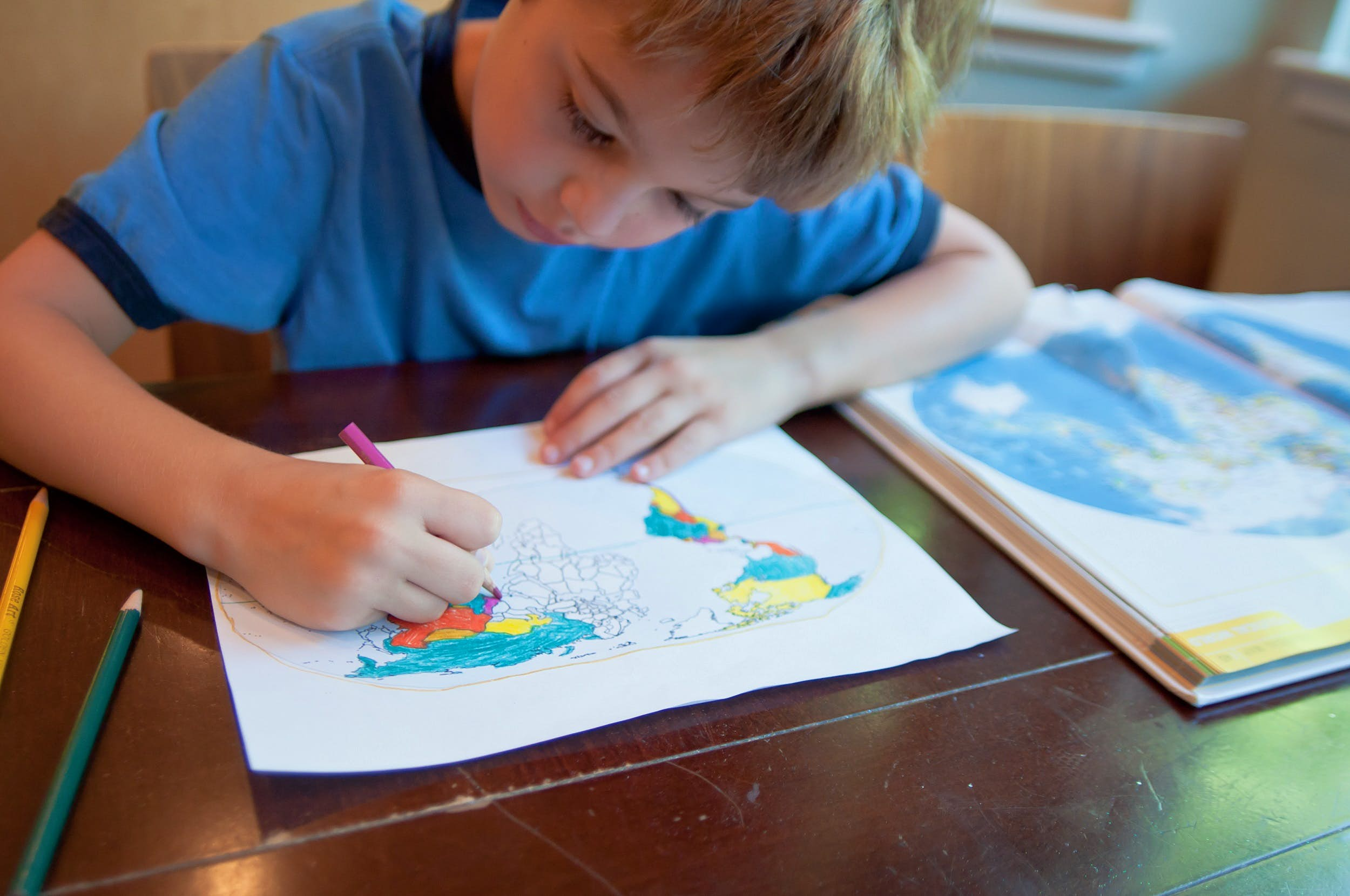A young boy leans over his world map that he's colouring in. Next to him is an open atlas