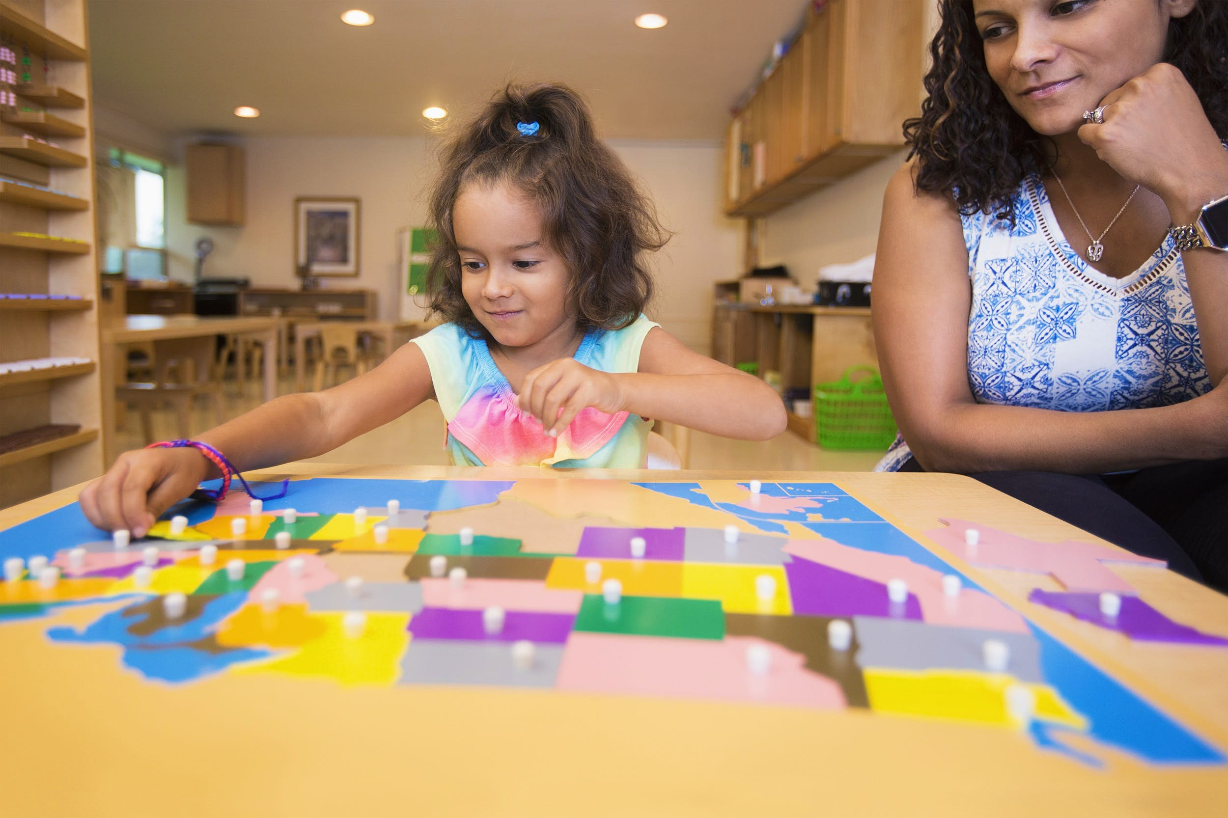 A young girl places the final pieces in a colourful jigsaw of the USA, while an adult watches on