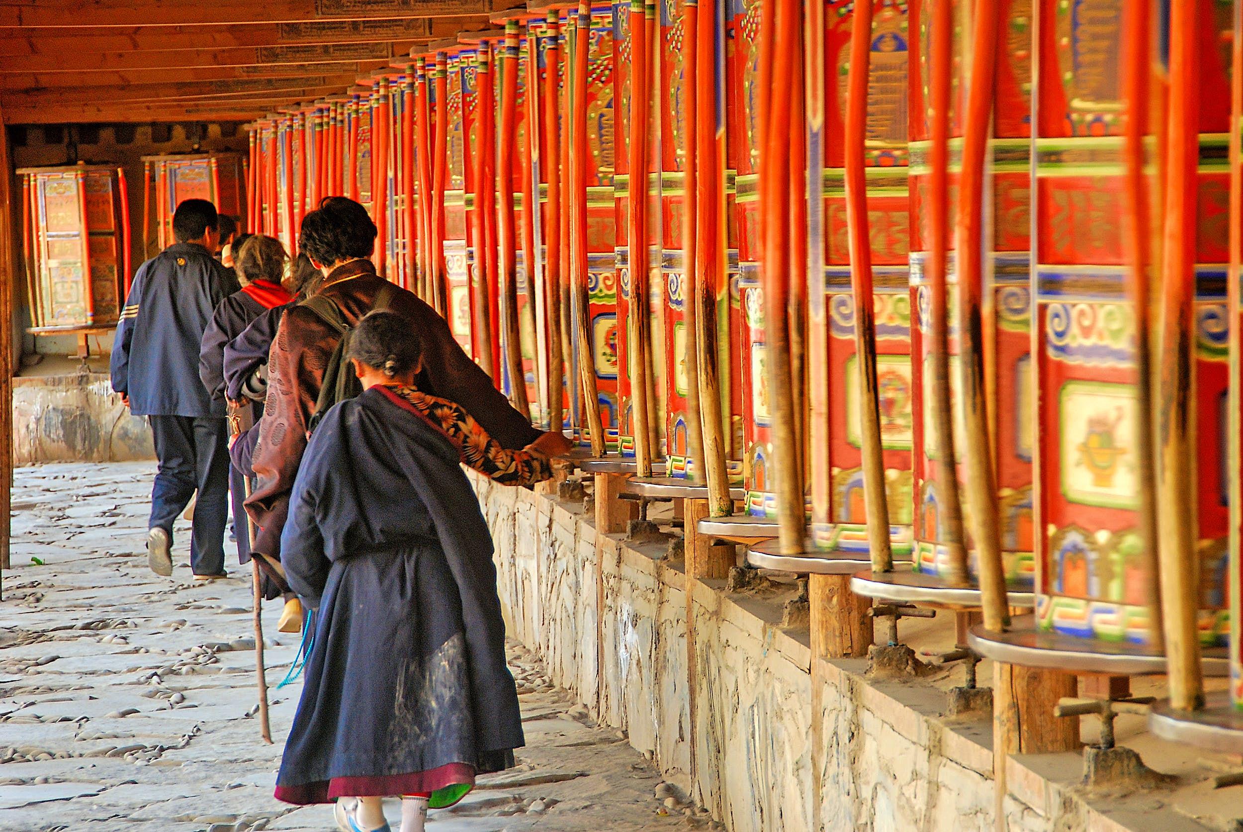 People walk past red prayer wheels.