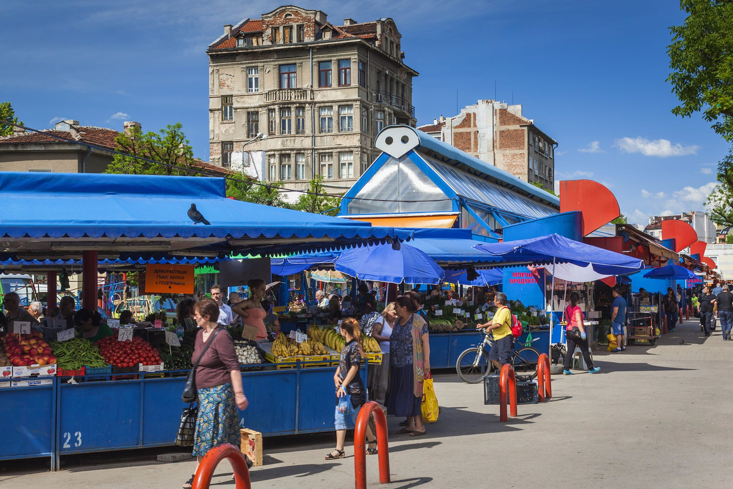 Shoppers stroll by a series of stalls packed with fruits and vegetables under a bright blue canopy