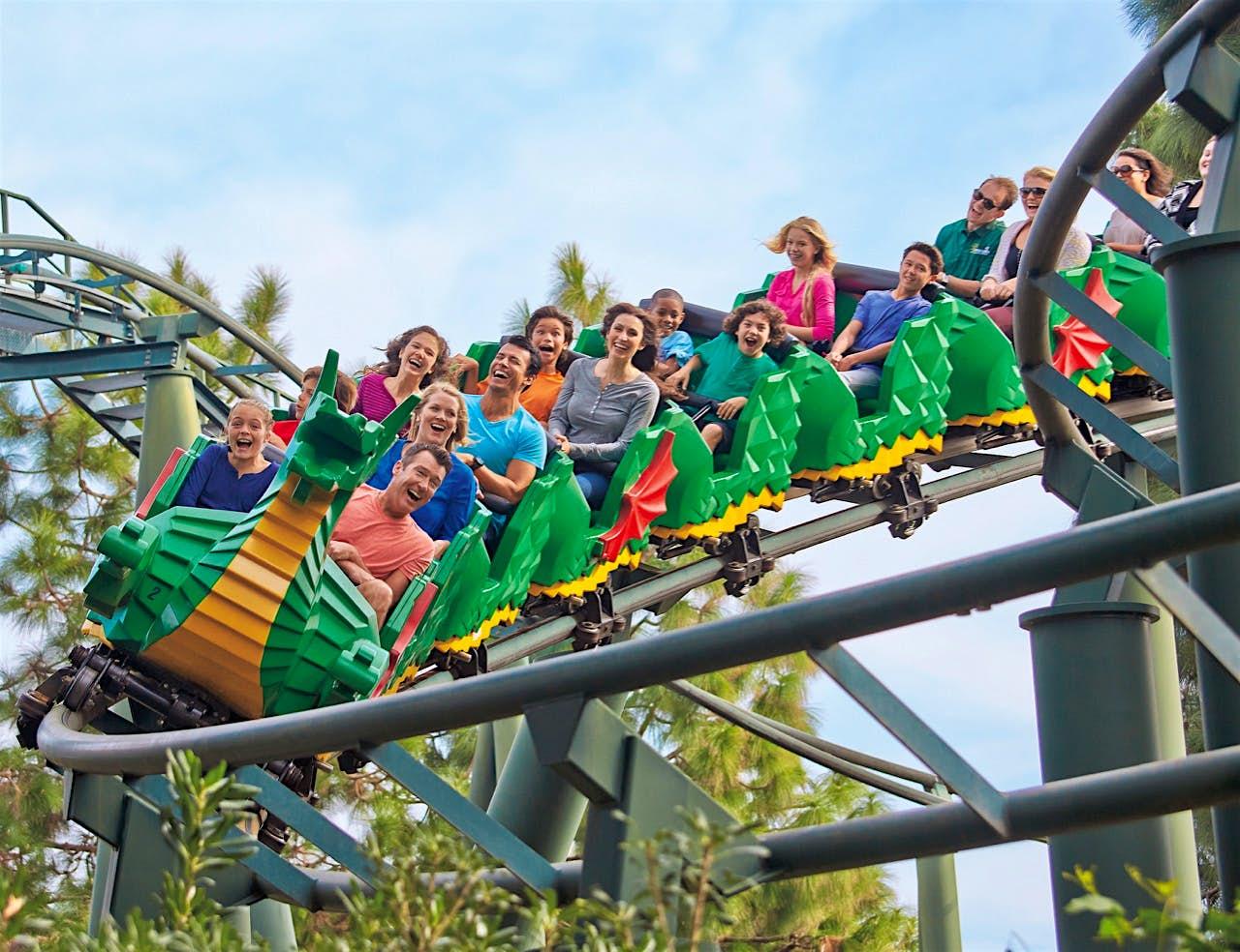 Pessoas andando na montanha russa Legoland New York - uma montanha russa projetada para parecer um dragão feito de tijolos Lego verdes, laranja, amarelos e vermelhos