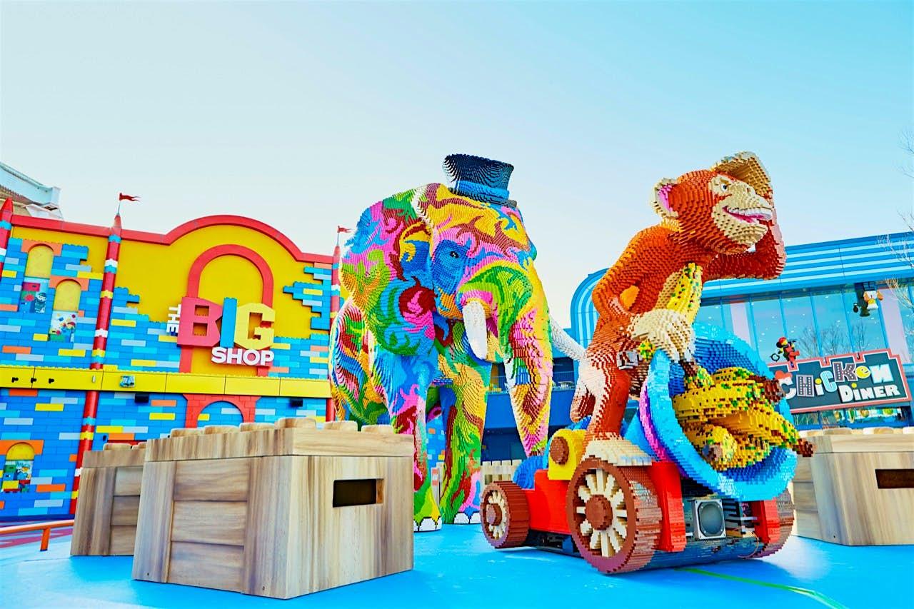 Entrada para a Grande Fábrica de Legoland em Nova York, com um macaco em um carro segurando um chapéu cheio de bananas e um elefante multicolorido em uma cartola
