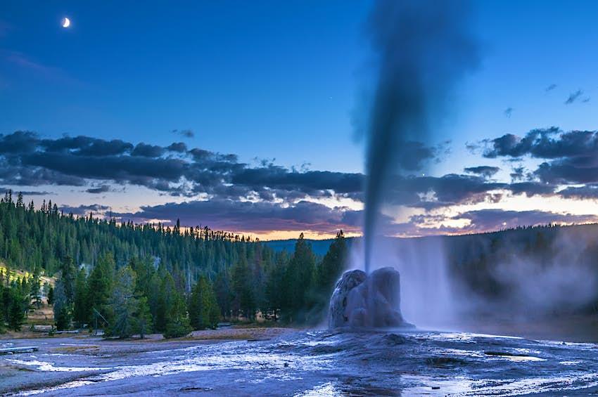 A geyser erupts at dusk