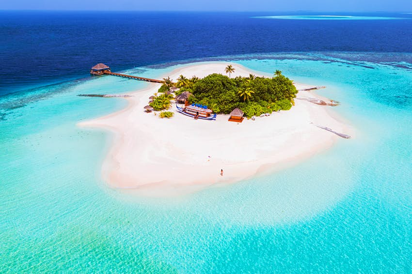 Ảnh chụp một hòn đảo cát nhỏ được bao phủ bởi những cây cọ trên không.  Có một bến tàu bằng gỗ trải dài ra bãi đá ngầm ở rìa đảo