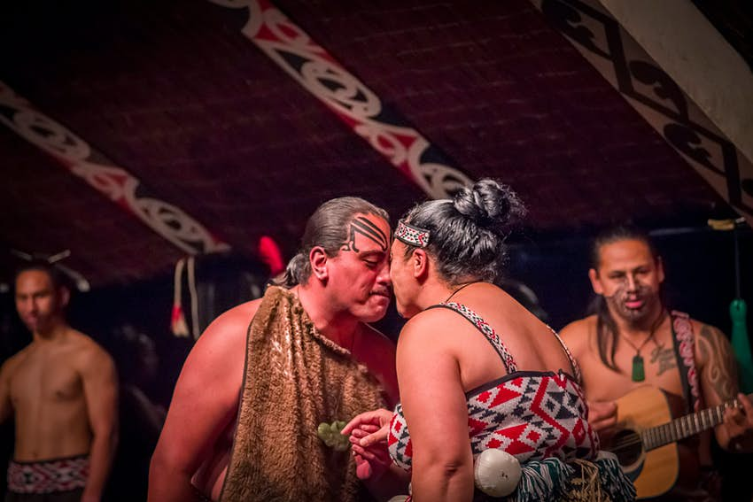 A Māori couple in traditional dress touch noses as they dance at Tamaki Cultural Village in Rotorua