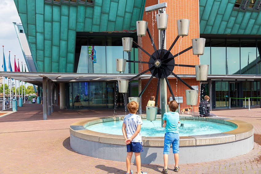 Two children stand watching a water wheel where cups of water are lifted as the wheel rotates