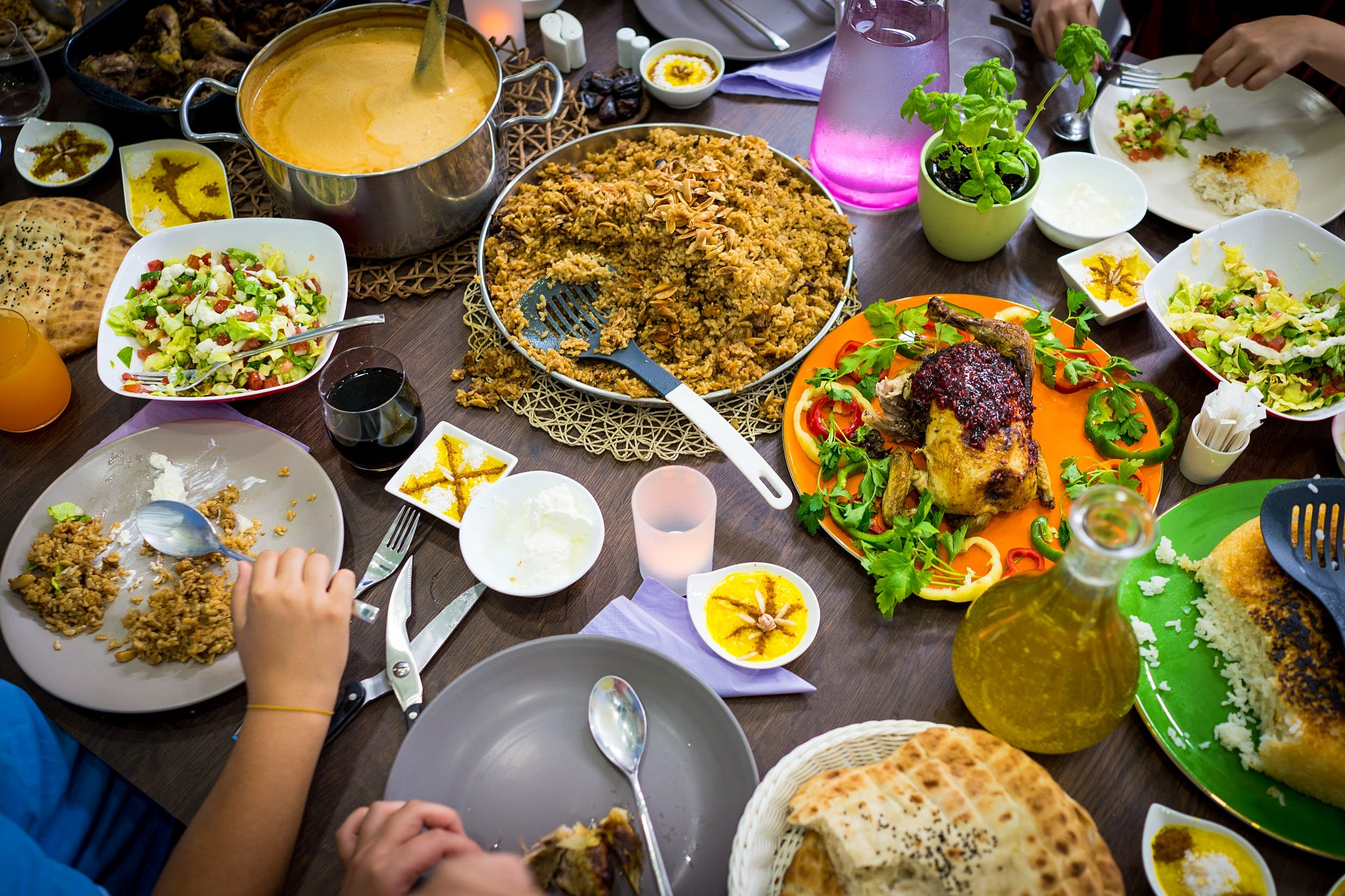 An aerial view of a table covered with different dishes, including rice, a curry dish, roasted chicken and a salad