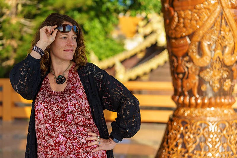 The author poses in Thailand, hand on hip, lifting sunglasses off her head