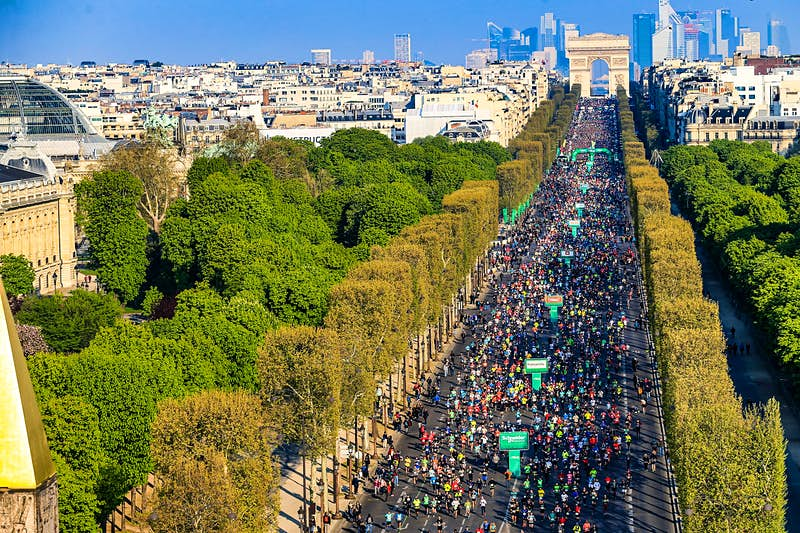 Under a cloudless sky tens of thousands of runners make their way from the Arc de Triomphe down the tree-lined Champs-Élysées.