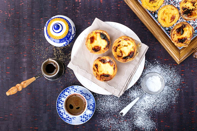 Three pastel de nata (Portuguese custard tarts), with browned tops sit on a plate; next to this is a shot of espresso (atop a blue-and-white saucer), a jar of honey and a small sieve with icing sugar