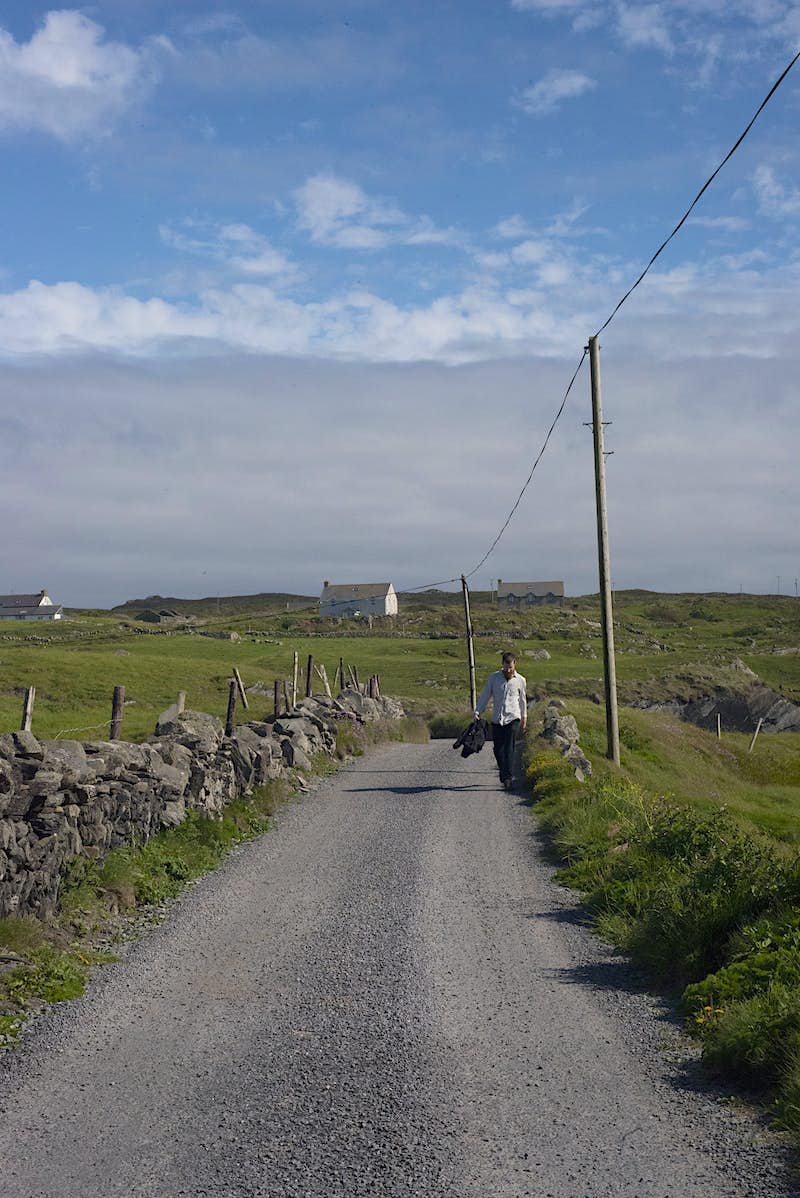 A man walks down a narrow rural road carrying his jacket. There are stone walls on either side and green fields all around.