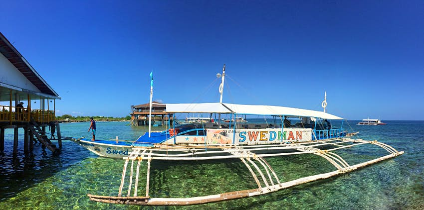 A worn white catamaran diveboat in the Philippines sits in shallow water dappled with light. In large rainbow letters on the side the name of the boat reads Swedman.