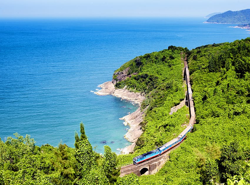 An aerial photograph of a train crossing a small bridge along a heavily forested section of coastline; a deep blue sea sits off the rocky shore that meanders in and out of the image.