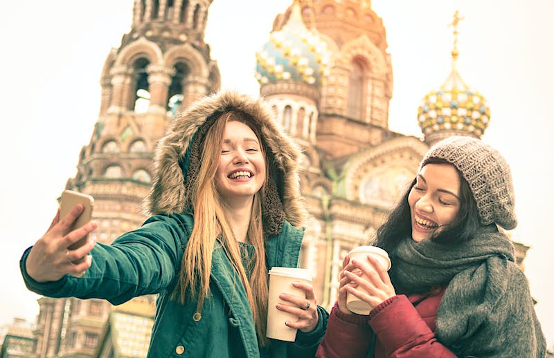 Two laughing girls take a winter selfie outside the Savior on Spilled Blood church in Saint Petersburg, Russia.