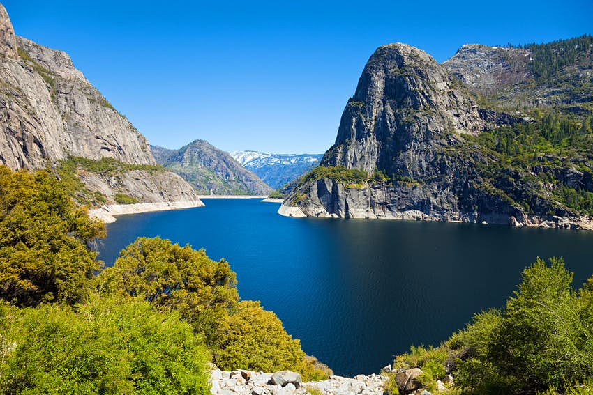 Hetch Hetchy Reservoir with blue sky above in Yosemite National Park.