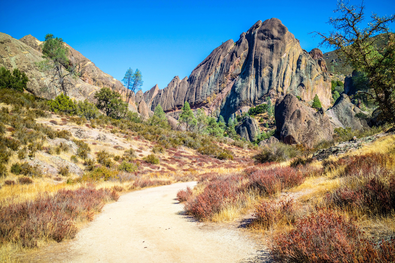 Natural rock formation, shaped like a pyramid, rising above a flat walkway in Pinnacles National Park