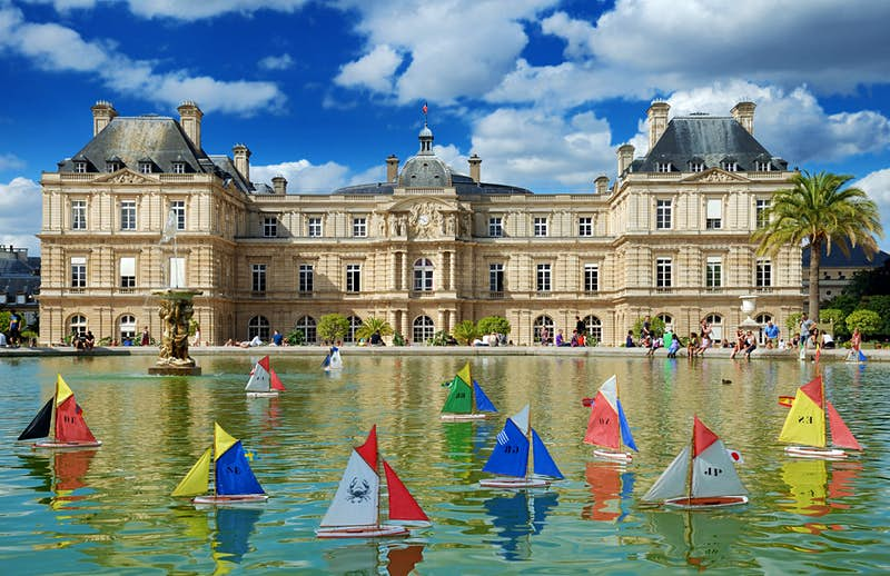Colourful wooden toy boats sail on the still waters of the pond in Jardin du Luxembourg, Paris. There is a stately building with beige bricks in the background underneath a clear blue sky.