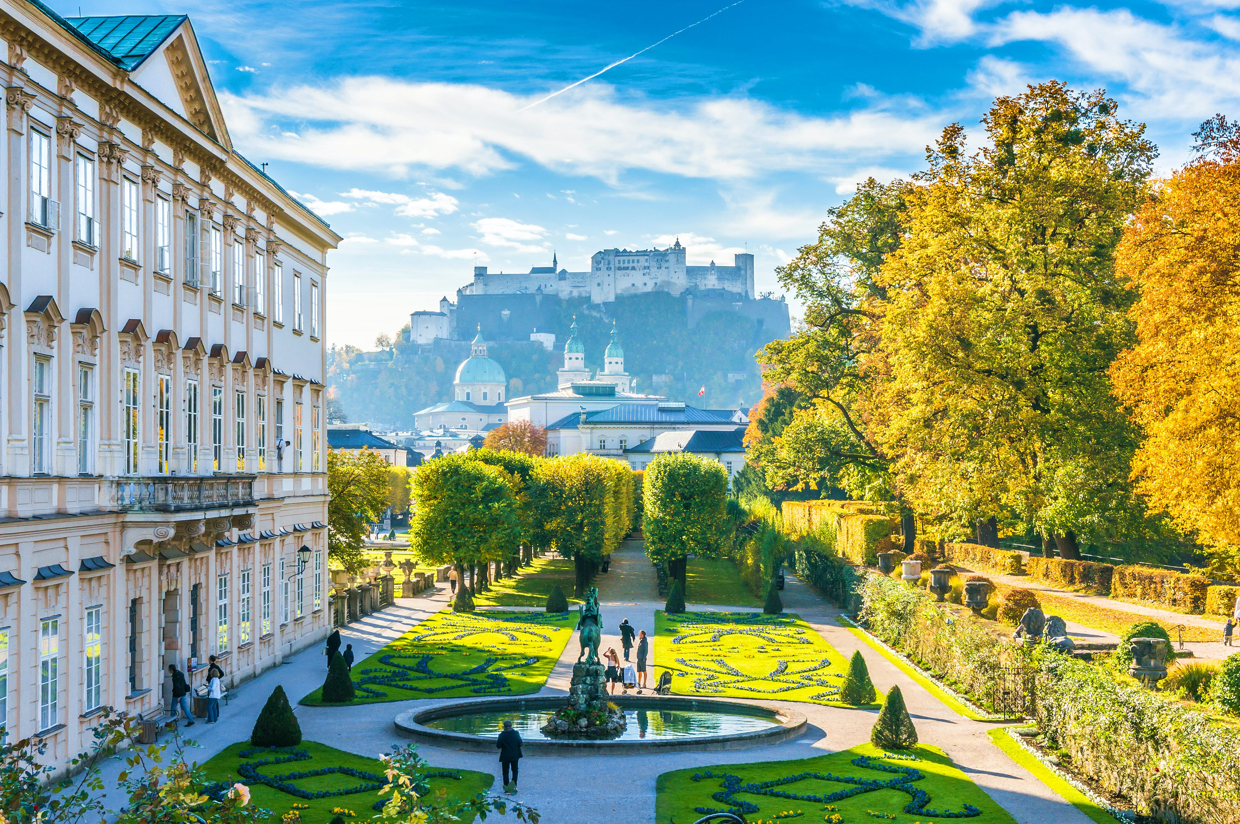 A view from Salzburg's Mirabell Gardens with the city's hilltop fortress in the background. The buildings are grand and white while the gardens are green and neatly manicured.