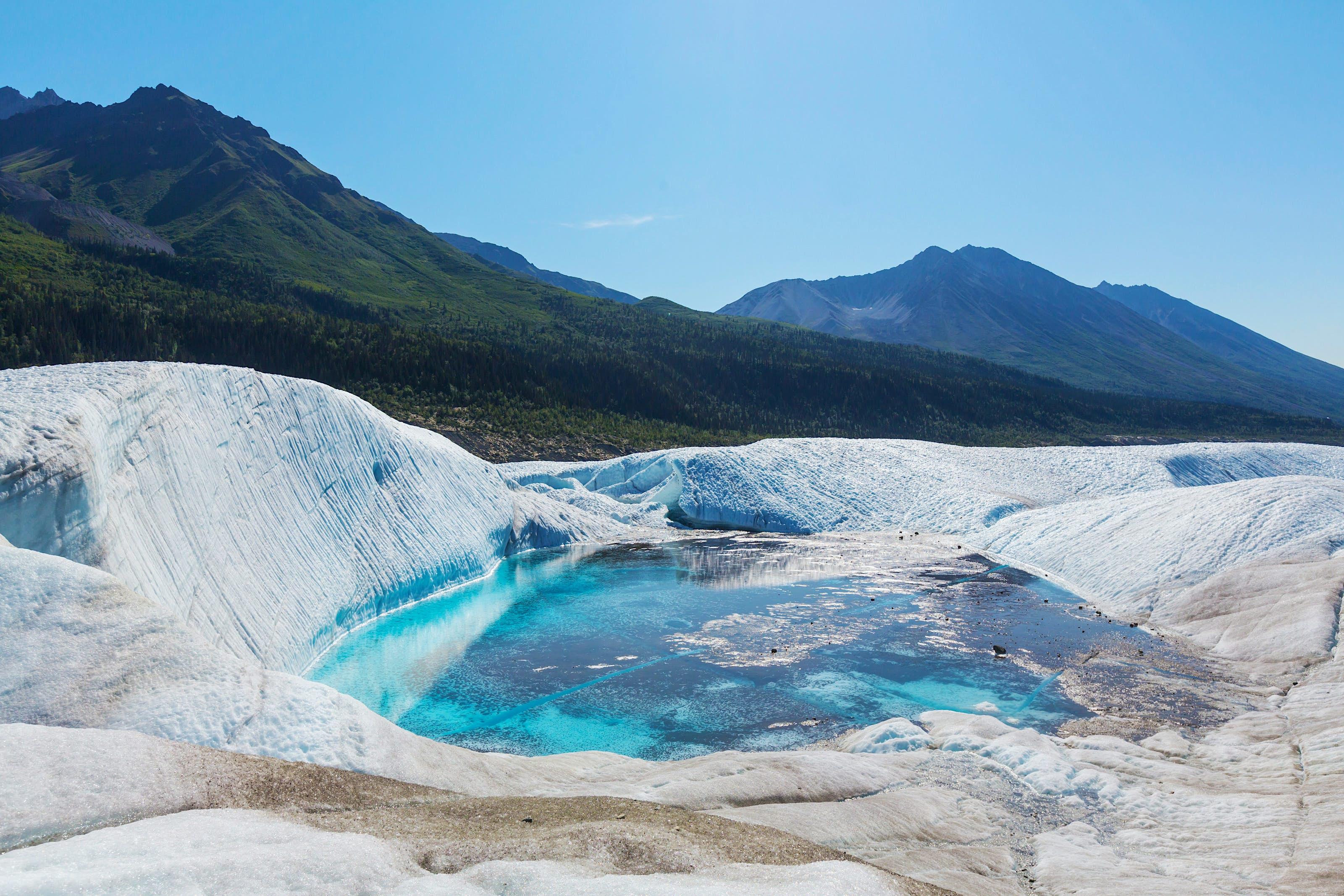 Vivid blue lake contrasting against the glacial ice of Alaska's Wrangell-St. Elias National Park