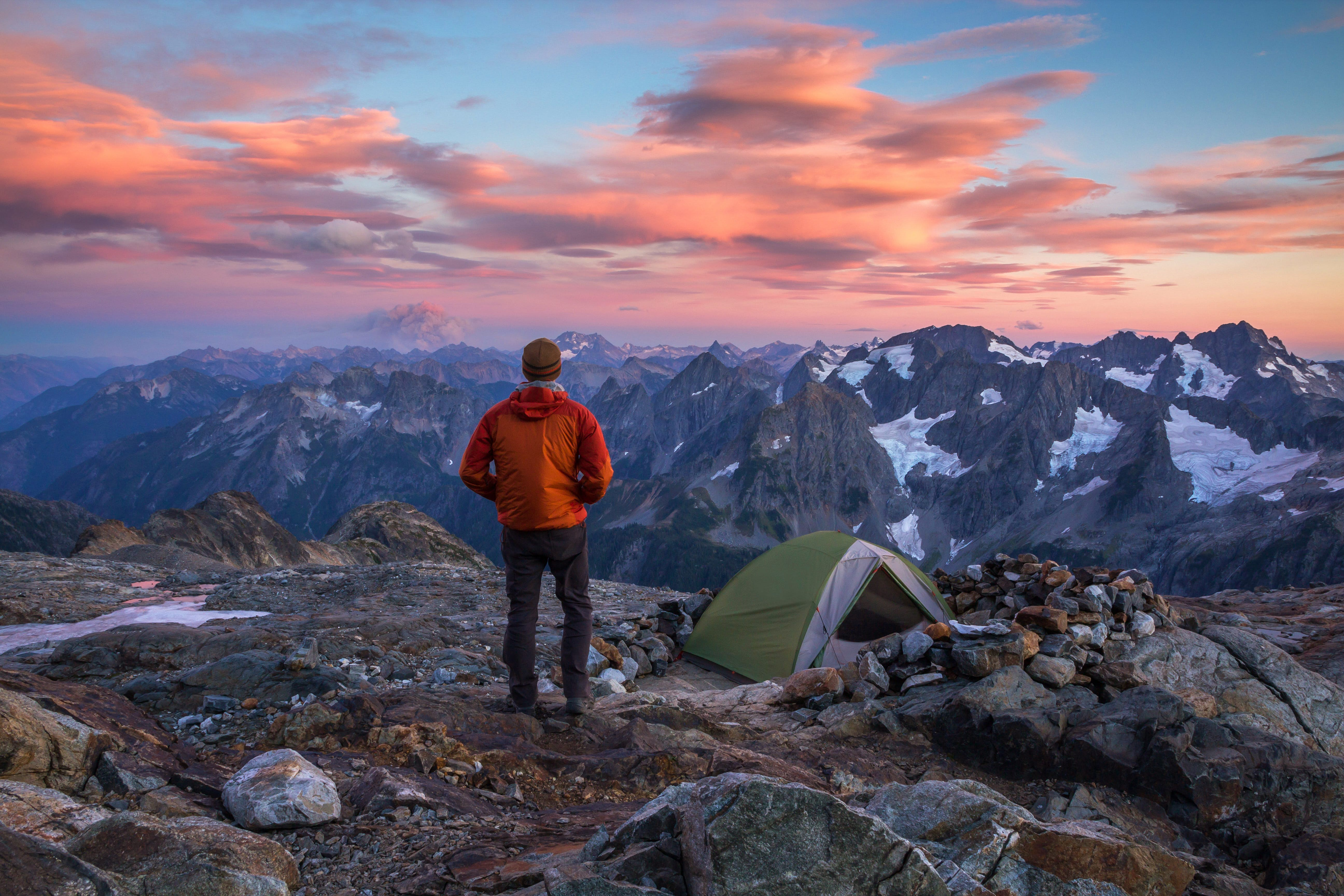 Hiker in warm clothing standing at their mountain-top camp, watching the clouds glow sunset colors above the mountains in North Cascades National Park