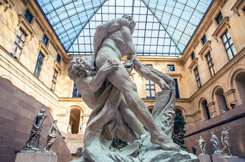 Sculpture hall of the Louvre museum, Paris, with the image focusing on the Milo of Croton statue: a man with his hand stuck in a tree being devoured by a lion
