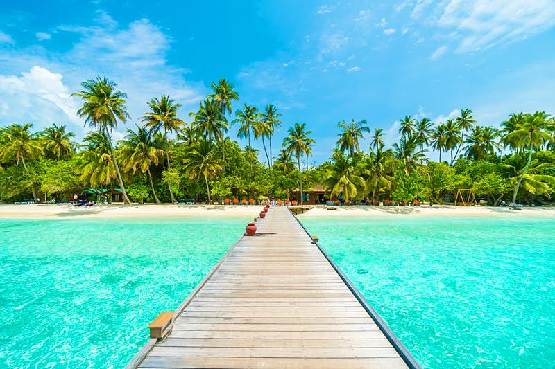 A wooden walkway extends across the sea to a beach in the Maldives