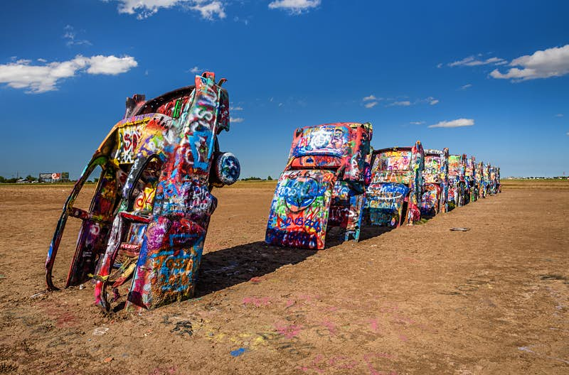 A row of 10 Cadillacs with their hoods buried in the earth stretches out. Each one is covered in colorful marks and graffiti