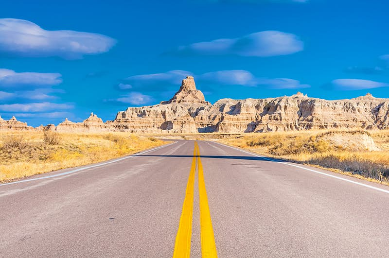A straight empty road stretches through Badlands National Park, with large rock formations in the distance against a blue sky