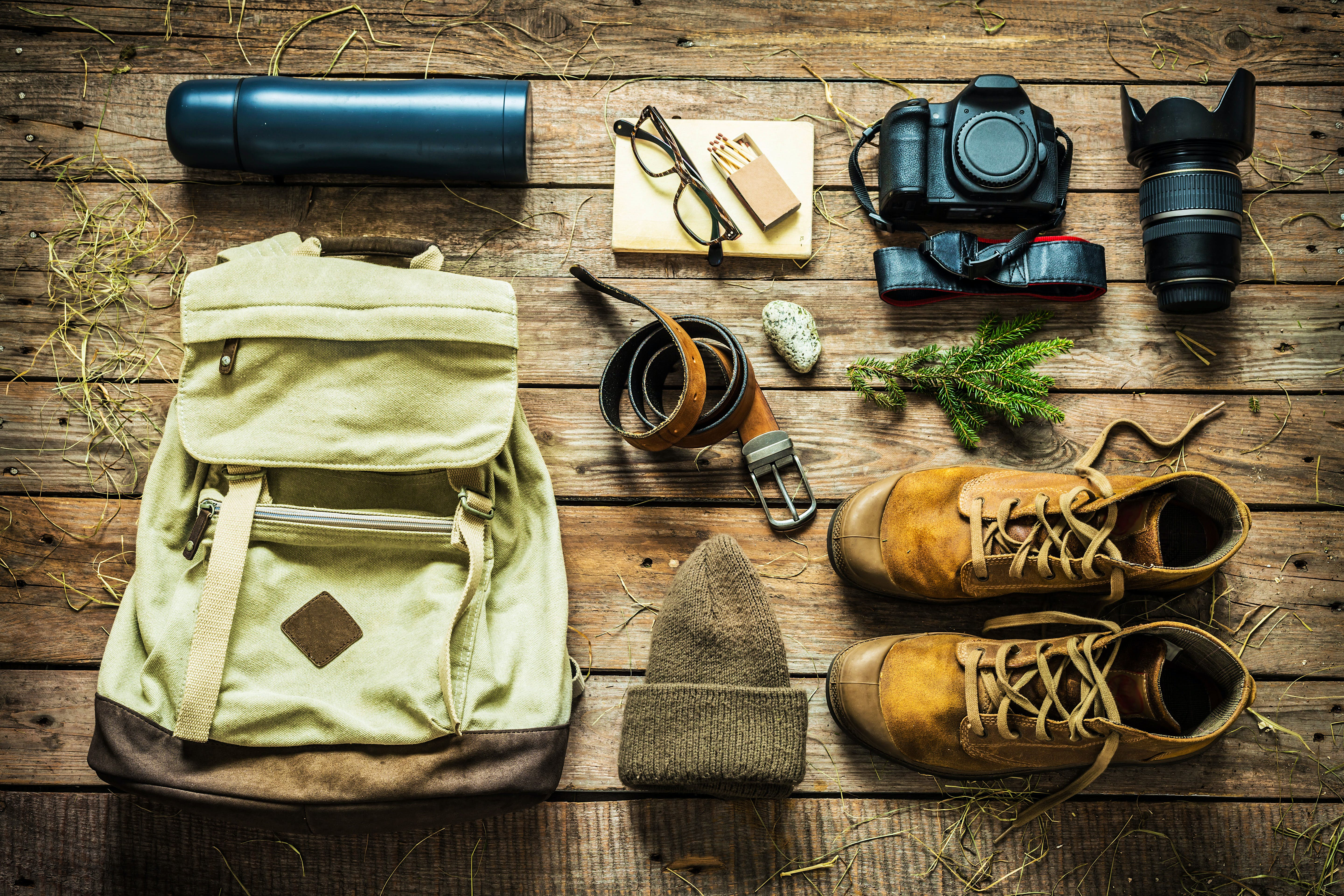 Items including boots, a hat, a belt, a thermos and a camera are laid out neatly on a wooden floor, ready to be packed.