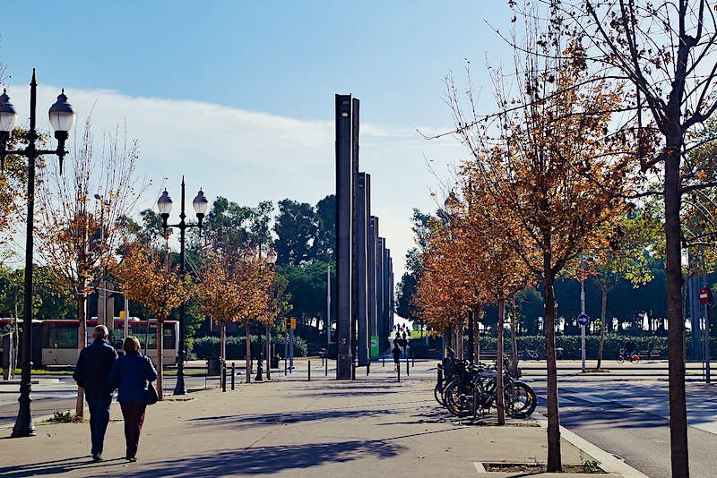 People walking down Rambla del Poblenou; the esplanade is lined with ornate lamp-posts and trees in autumnal colours, and there are sculptural columns further along the Rambla.