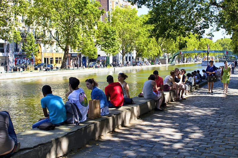 Groups of people sit on the small wall that runs along the banks of Canal St-Martin, a canal in central Paris on a sunny day.
