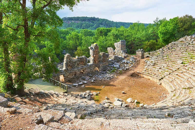 Looking down over the remains of the stone semicircular theatre at Troy; there are trees and a verdant valley beyond.