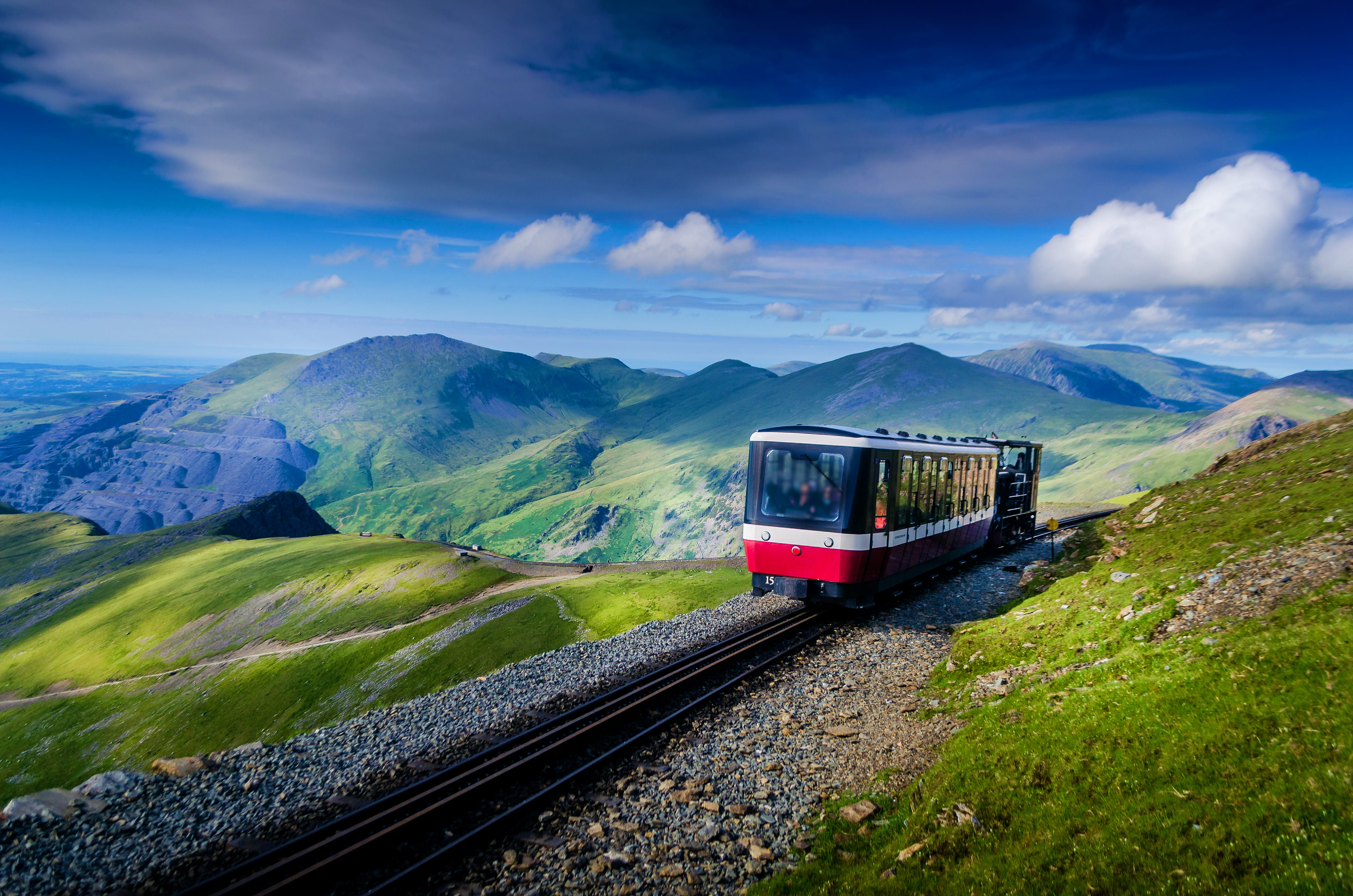 A small red, narrow-guage tourist train rides the rails towards Snowdon in Snowdonia National Park, as sun bathes the green peaks of the range.