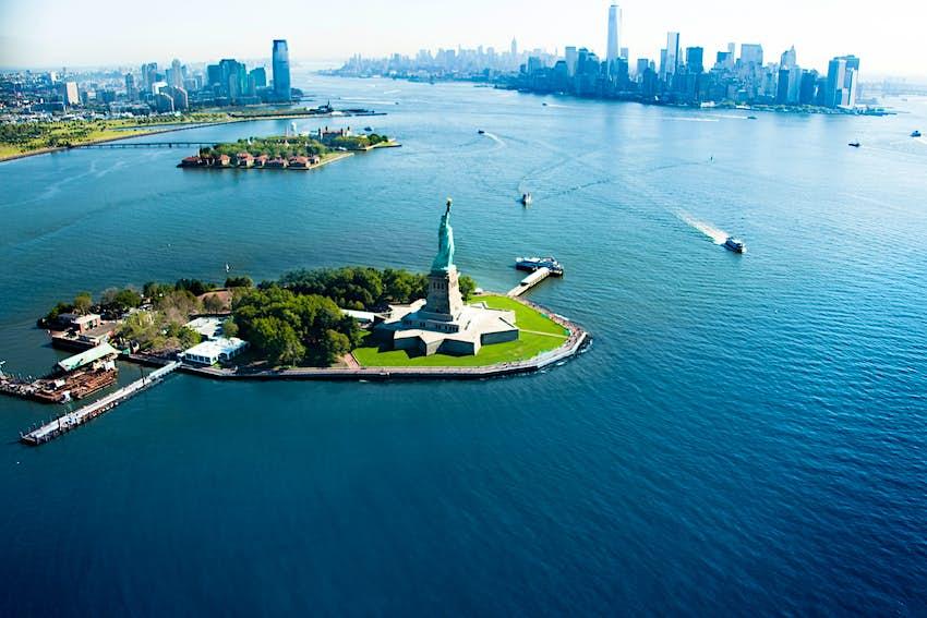Bức tượng trên một hòn đảo nhìn từ trên không với đường chân trời thành phố phía sau