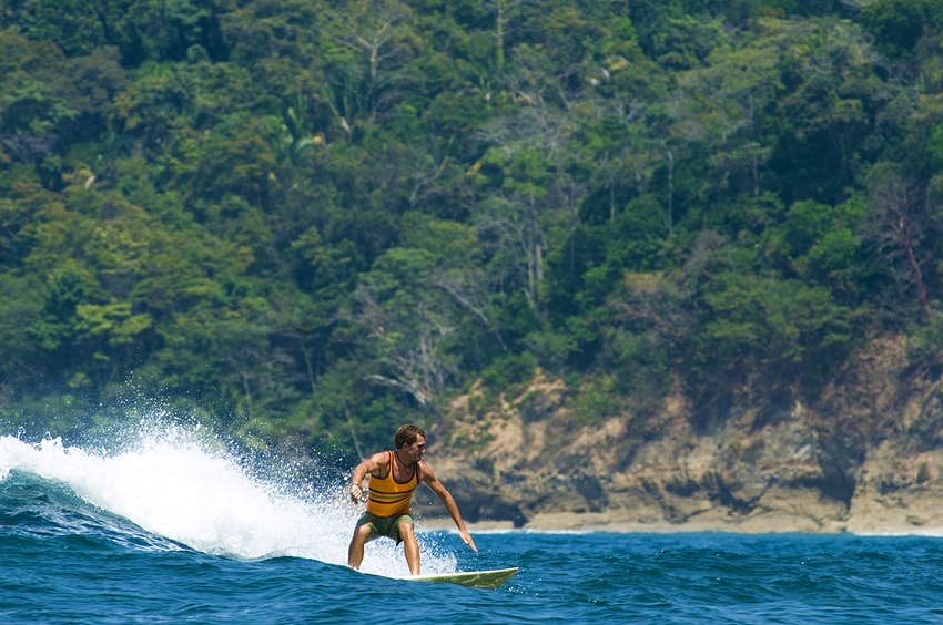 young man surfing a wave on the coast of Dominical; he's riding left to right, with the tree covered rocky cliffs in the background