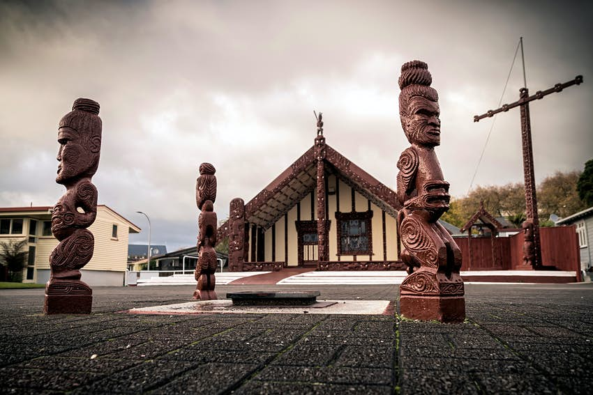 Intricately carved wooden sculptures of people stand outside the Tama-te-Kapua Meeting House in Ohinemutu, Rotorua.