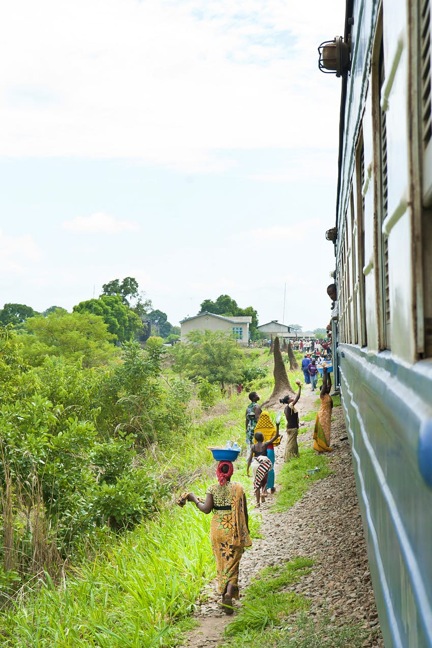 Women walk along the gravel verge beside a stopped train; they carry bowls on their heads and sell drinks and food through the windows of the train.