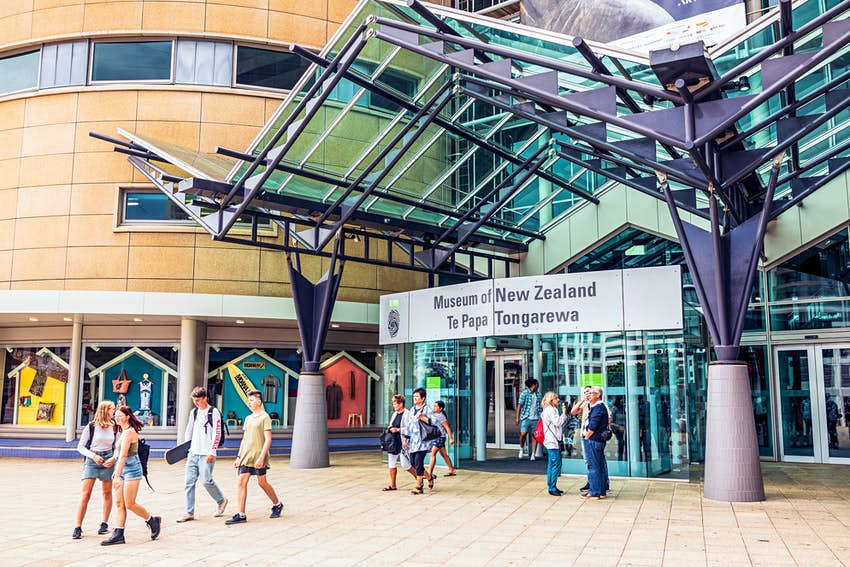 Visitors entering and leaving the Museum of New Zealand in Wellington; the sign also states the Māori name, Te Papa Tongarewa.